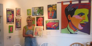 Nanci Killingsworth stands before Marcia Gawecki's Pop Art portraits